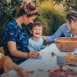 a happy multigenerational family enjoying lunch outdoors by MultiGen